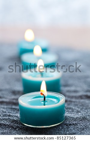 Close-up of blue candles on silver sand - stock photo