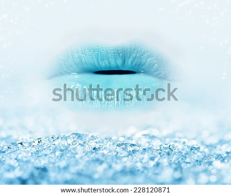 Close-up of blue girl lips with mist and icy snow, beauty and winter concept - stock photo