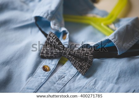Close-up of blue shirt with a bow tie on a hanger. Black bow tie with scientific symbols. Clothes. Special occasion suit. Clothes on a hanger. - stock photo