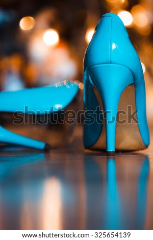 close-up of blue / turquoise party shoes with golden bottom. Selective focus on the heel tap area.. - stock photo