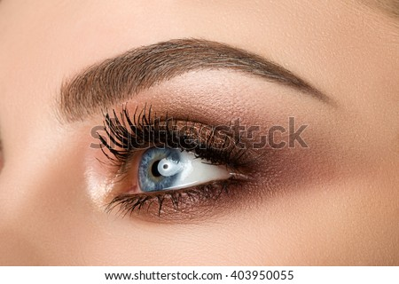 Close up of blue woman eye with beautiful brown with red and orange shades smokey eyes makeup. Modern fashion make up. - stock photo