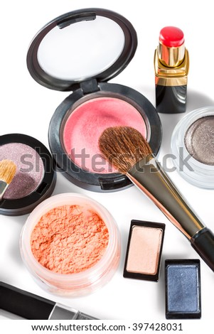 Close up of blush, eye shadow, red lipstick, makeup powder and thick brush on white background