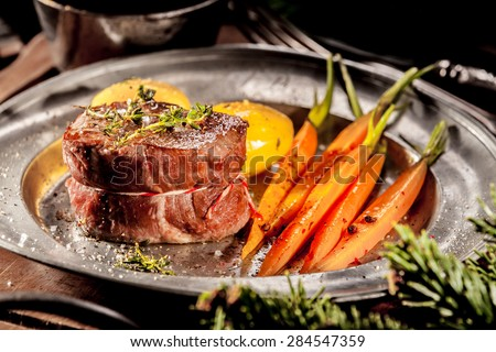 Close Up of Boar Steak Served on Metal Plate with Carrots on Wooden Tray with Evergreen Sprigs - stock photo