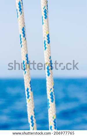 Close-up of boat ropes with sea and sky in the background - stock photo