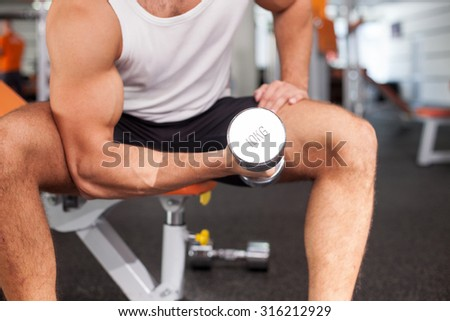 Close up of body of sportsman training in fitness center. He is sitting on bench. The man is raising dumbbell l with efforts - stock photo