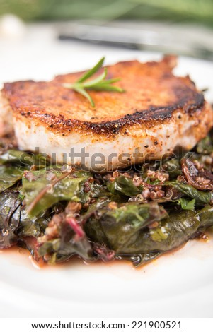 Close up of Boneless Grilled Pork Chop Served with Wilted Rainbow Chard and Collard Greens  - stock photo