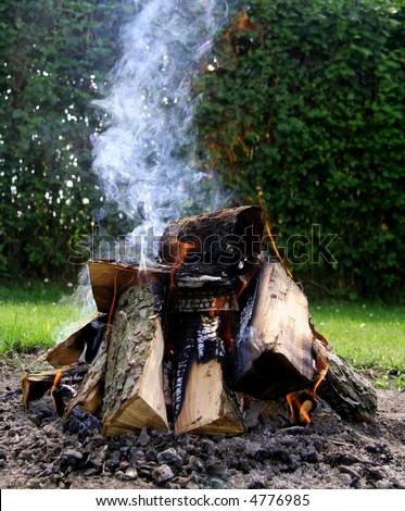 Close-up of bonfire with smoke, fireplace. - stock photo