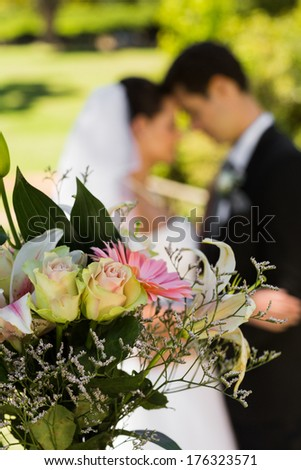 Close-up of bouquet with blurred newlywed couple in background at the park - stock photo