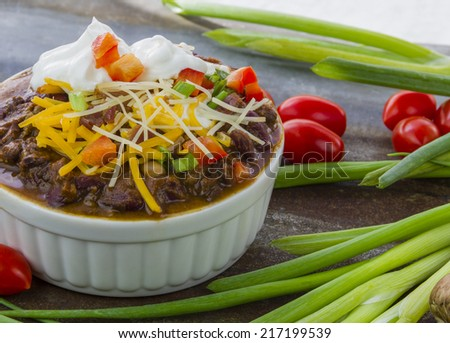 Close up of bowl of chili with sour cream. cheddar cheese, scallions and tomatoes  - stock photo