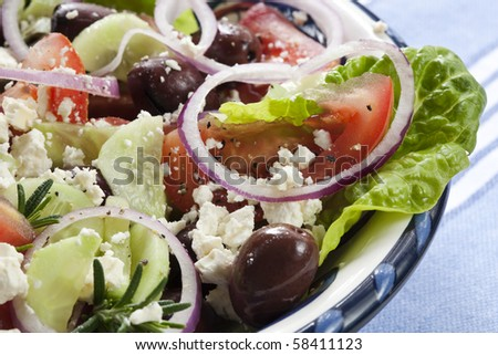 Close-up of bowl of Greek salad.  Luscious vine-ripened tomatoes, with feta cheese, kalamata olives, cucumber, red onion, kos lettuce and rosemary. - stock photo