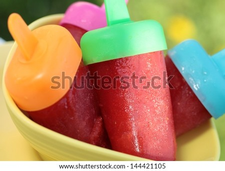 Close-up of bowl with homemade strawberry popsicles. Selective focus, shallow DOF.