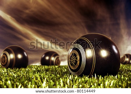 Close up of  bowling balls on an open bowling field at sunset - stock photo