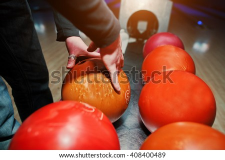 Close up of bowling player hand taking orange ball from bowl lift - stock photo