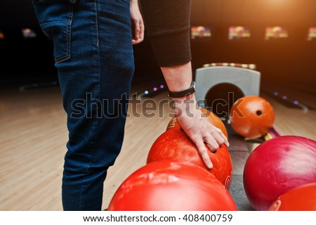 Close up of bowling player hand taking red ball from bowl lift - stock photo