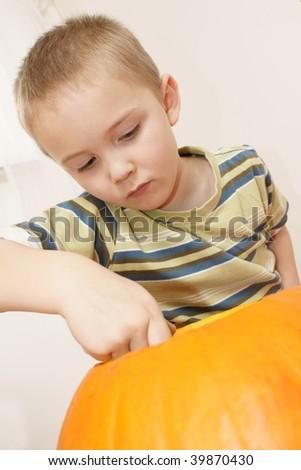 close up of boy carving pumpkin - stock photo