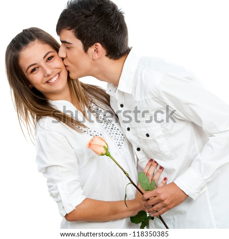 Close up of boy giving girlfriend a rose and romantic kiss.Isolated. - stock photo