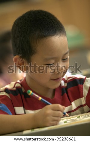 Close up of boy writing at desk