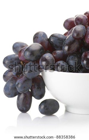 Close-up of branch of purple grape in white bowl on white background. - stock photo