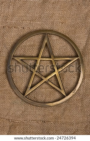 close up of brass pentagram / pentacle on burlap - hessian background