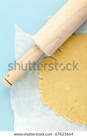 Close up of bread dough with rolling pin - stock photo
