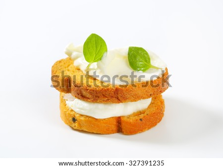 close up of bread rusks with cream cheese on white background