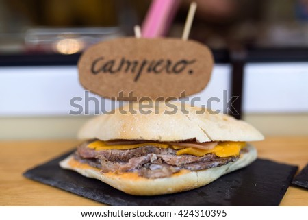 Close-up of bread with hamburguer, cheese and ham in a food truck. - stock photo