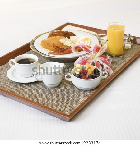 Close-up of breakfast tray laying on white bed. - stock photo