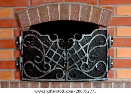 Close up of brick fireplace with an iron gate - stock photo
