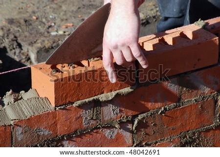 Close up of bricklayer at work - stock photo