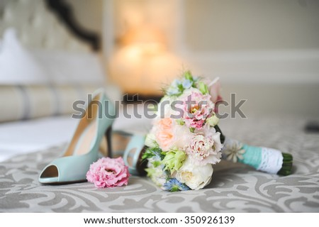 close-up of bridal bouquet of roses, wedding flowers for the ceremony on the bed in a hotel room with blue shoes - stock photo