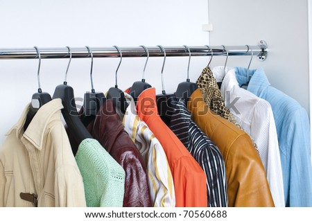 close up of bright clothes on hangers - stock photo