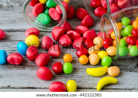 Close-up of bright colorful candies scattered on table from glass jars - stock photo