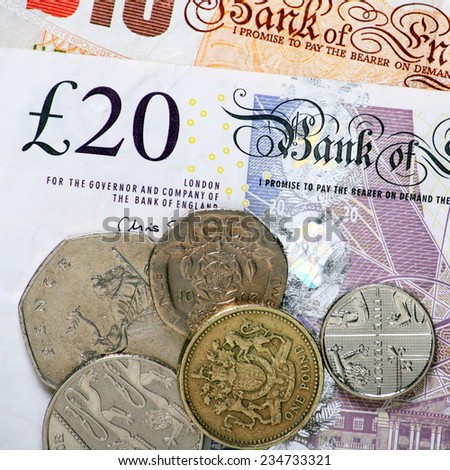 Close up of British currency with twenty and ten pound notes alongside various coins, including the fifty, twenty and ten pence pieces - stock photo