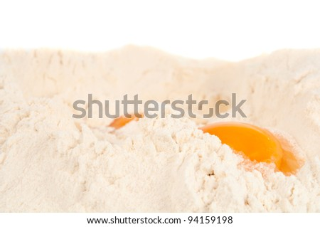 Close up of broken eggs in white flour for making pasta - stock photo