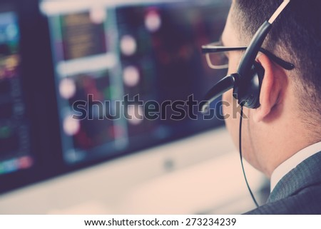Close-up of broker in a headset analyzing data on the computer screen, selective focus - stock photo
