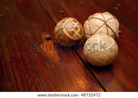 Close-up of Brown wooden sleeper table with holes and handmade ornamental balls