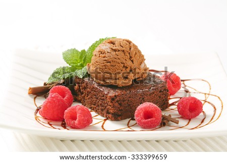 close up of brownie cake with scoop of chocolate ice cream and raspberries on white plate and place mat - stock photo