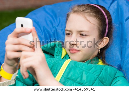 Close Up of Brunette Girl Wearing Jacket and Pink Headband Using Modern Cell Phone Outdoors While Relaxing on Cozy Blue Bean Bag Chair