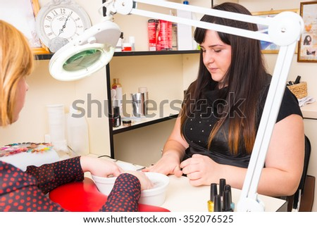 Close Up of Brunette Manicurist Preparing Tools While Blond Woman Soaks Hands in Small Bowls of Water During Spa Manicure Treatment - stock photo