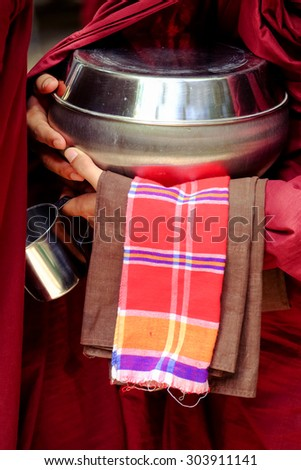 Close up of buddhist monk in a robe and his hands holding a bowl and cup - stock photo