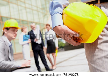 Close-up of builder holding helmet with working group at background - stock photo