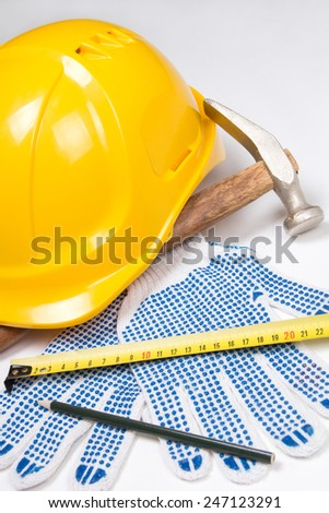 close up of builder's tools - helmet, work gloves, hammer, pen and measure tape over white background - stock photo