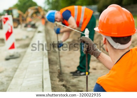 Close-up of builders working along on a building site - stock photo