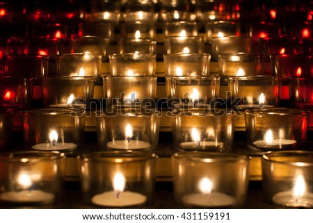 close up of burning candles in white and red transparent chandeliers in a church as an abstract background, horizontal - stock photo