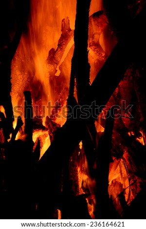 Close up of burning logs in the fireplace on black background