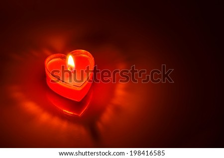 Close Up of burning red candle heart on dark background - stock photo