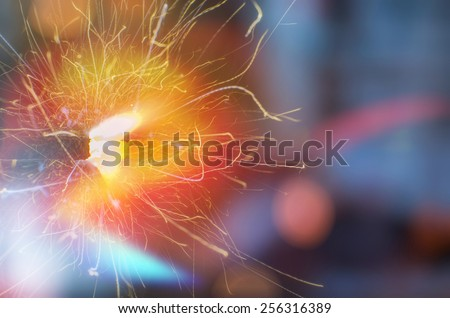 Close up of bursting sparkles on dark background - stock photo