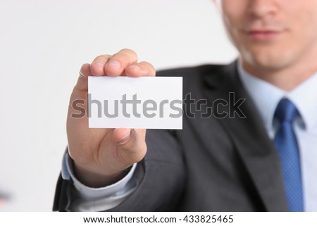 Close-up of business card in business mans hand.