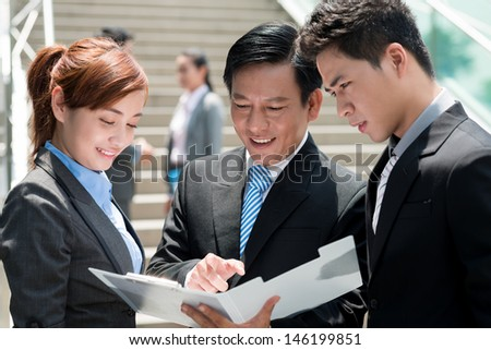 Close-up of business colleagues standing and communicating outside