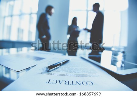 Close-up of business contract with pen at workplace on background of office workers interacting - stock photo